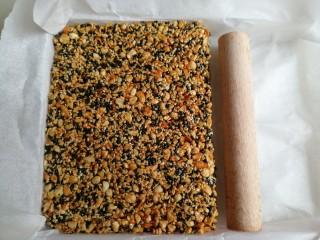 花生芝麻糖,趁热倒入铺了油纸的牛轧盘里,迅速用擀面棍压紧压实