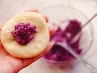 奶香四溢的紫薯小餐包,把静置松弛好的面团,用手摁扁后,加入适量的紫薯馅。