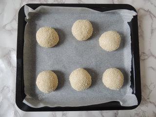 芝麻葱花面包,做好之后摆放到铺了油纸的烤盘里,每个面团之间要留出发酵的空间。