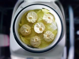 麻辣豆腐粉条香菇包,放在蒸锅上,凉水开始蒸。我没有用笼布,为了防粘,垫了一层白菜叶子,也可以在包子底下抹一层油防粘哦,根据自己习惯来。