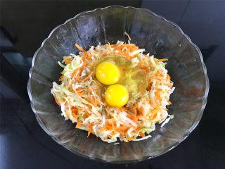 萝卜丝饼,加入少许盐和胡椒粉,再打入2个鸡蛋,搅拌均匀。