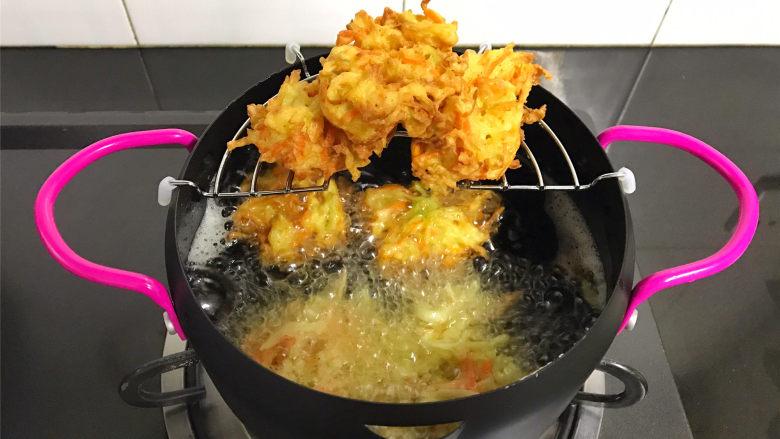 萝卜丝饼,等炸到可以定型后翻面炸另一面,其间要用筷子翻拌一下,防止糊锅,炸至两面呈金黄色后捞出控油。