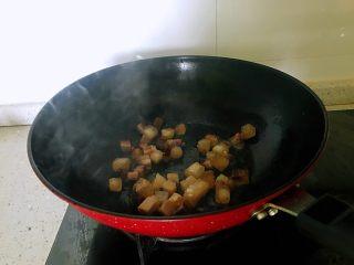 小炒腊肉丁,锅置于火上,放一点点油,下入腊肉,炒至出油。(腊肉丁中有肥肉,会有油出来)