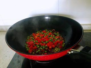 小炒腊肉丁,下入洋葱、姜蒜,翻炒约1分钟出香味时倒入豌豆和柿子椒,翻炒2分钟,放盐,炒匀。
