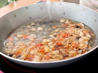 菌菇豆腐羹,倒入虾皮和蘑菇碎,继续翻炒几下,倒入适量清水,煮沸