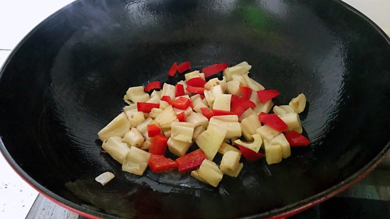 糖醋藕丁,锅中放少许油,下藕丁翻炒,下柿子椒,翻炒1分钟。