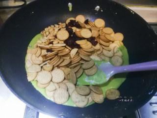 抹茶雪花酥,倒入温热的熟花生仁、蔓越莓干和韧性饼干,燃气灶立即关火