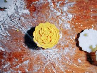 紫薯南瓜糯米糕,取月饼模具,按压出花形。(我的月饼模具是50g的,所以面团约30g,里面包的紫薯花生丸约20g,大家可以根据自己模具的大小来分剂子。)月饼模具上要抹点油哦,防黏。