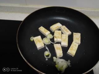 豆腐炒黄豆芽,放入葱碎。