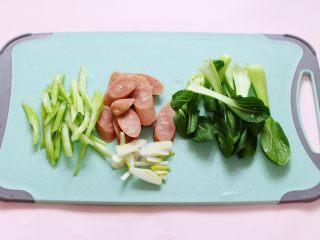 营养又养胃的快手火腿肠芹菜炒面,火腿肠斜切成薄片,芹菜斜切成丝,葱切丝,小油菜撕开。