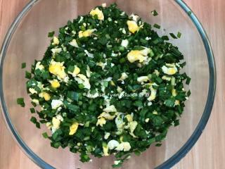 韭菜盒子,加入玉米油轻轻翻拌均匀,千万不可以过度搅拌,让每片韭菜都被油裹住,这样韭菜才不会出太多的汤汁, 然后把晾凉的鸡蛋倒入韭菜中,加入适量的盐轻轻翻拌均匀即可,盐一定要开始包的时候再加入,先加盐会让韭菜出汁的,这一点一定要注意