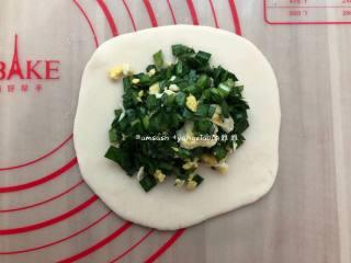 韭菜盒子,取一个小剂子擀成大圆饼皮,码上韭菜鸡蛋馅