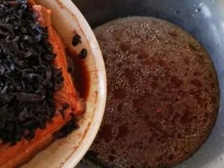 梅菜扣肉,取出蒸好的大碗,放至不烫手后用手端着碗,轻轻蓖出汤汁至锅里。