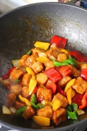凤梨菠萝咕噜肉,加黄.红.绿.灯笼椒翻炒,加入炸好的里脊肉块,加糖,醋,番茄酱,盐翻炒