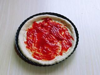 披萨新吃法~奥尔良鸡丁披萨,取一块面团擀成与披萨盘一样大的披萨皮,再用叉出洞洞,涂抹上番茄酱。