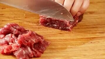 葱爆牛肉,将牛里脊清洗一下,逆着纹路切成薄片,越薄越好。