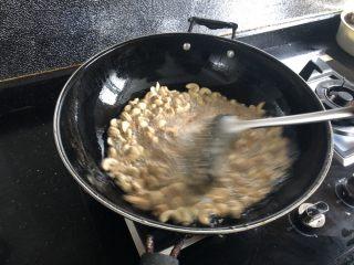 炸腰果,用漏勺不停地搅拌,让所有的腰果受热均匀。