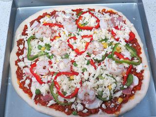 货真料足媲美必胜客的【海陆至尊披萨】,再撒一层马苏里拉芝士碎后放入青椒、红椒及熟虾仁,撒上玉米粒、豌豆粒,撒上最后一层芝士碎