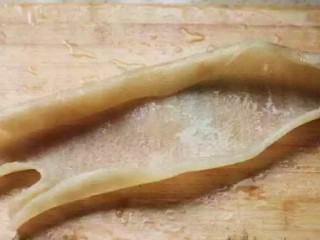灌汤小笼包,煮至肉皮变色后捞出,用刀将肥油剔除干净;