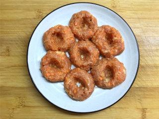 招财进宝,取适量拌好的肉馅团成肉丸,放在盘子中,然后在肉丸中间挖个洞。