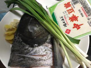 豆瓣酱千岛湖鱼头豆腐,首先我们准备好所有食材,青蒜摘洗干净,生姜去皮洗净之后切成片,大蒜去皮洗净之后切成片,大鱼头处理干净
