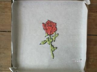 彩绘玫瑰蛋糕卷,在绘有玫瑰花的油纸反面根据线条勾勒出玫瑰花的形状,先用黑色面糊描边,再用红色面糊和绿色面糊分别填充花瓣部分和茎叶部分,画好后立即送入预热好的烤箱烘烤1分钟定型