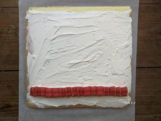 彩绘玫瑰蛋糕卷,将晾凉的蛋糕片放在干净的油纸上,没有彩绘玫瑰的那面朝上,四周切平整,底端45度斜切,然后抹上打发的淡奶油,铺上一排夹心用的心型红丝绒蛋糕,铺夹心的时候要挨着铺紧凑些,不能留有空隙