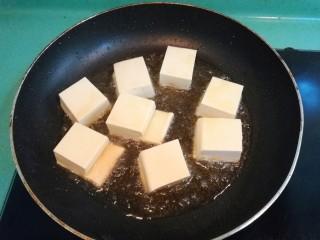 砂锅鱼头豆腐煲,接着把切好的豆腐放进锅里煎