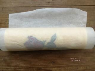 彩绘玫瑰蛋糕卷,利用擀面杖反卷底部油纸的方式慢慢推送蛋糕片,使蛋糕片自然往前卷起,卷好后油纸包起整条蛋糕卷,底边朝下放置,送入冰箱冷藏1小时定型