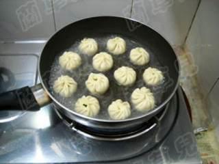 茼蒿鸡蛋生煎包,锅中倒油,将包子生胚码入锅中,中火煎2分钟定型。沿锅边淋入清水。