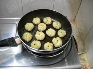 茼蒿鸡蛋生煎包,加盖继续煎至水分蒸发。淋入少许油,煎至底壳焦黄即可盛入盘中食用。