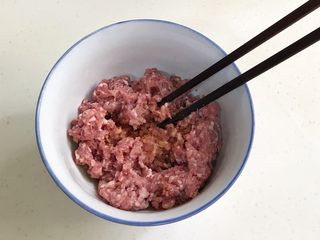 四喜蒸饺,往搅好的肉馅中加入姜末、生抽、料酒和盐,用筷子顺着一个方向搅拌上劲。