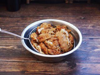 虾仁笃面筋(天津菜),用汤勺压一压笊篱里的面筋,把面筋控干水份备用。
