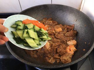 虾仁笃面筋(天津菜),放入黄瓜片和胡萝卜片且翻炒均匀。