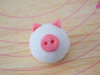 小猪花生流沙汤圆,取一个包好的汤圆,把猪鼻子和耳朵沾上水装上