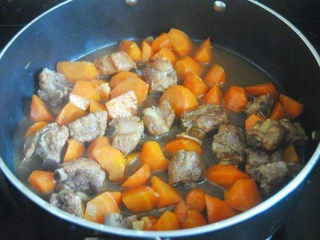 胡萝卜炖排骨,最后加入没过一般材料量的清水并调入盐,大火煮沸后转小火慢炖半小时至几近收汁即可;