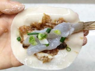 猪肉大虾煎饺,饺子皮先放肉馅,再放一个虾仁,再撒上葱花,中间包起来,留出二头。