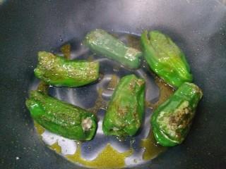 虎皮青椒酿肉,锅内放油烧热,再把包有肉的青椒放入油锅内煎。记得要勤翻面哦!