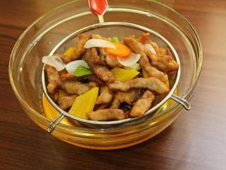 香檬糖醋里肌,将油温升高, 倒入肉条回炸, 蔬菜一起加入, 大火油炸, 将多餘水份逼出, 将锅内食材倒至滤网上, 沥掉多餘油脂