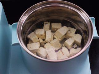 海蛎子豆腐汤,锅中倒入适量的清水烧开后,把切块的豆腐焯水后捞出沥干水份。