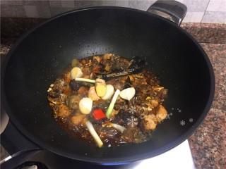 红烧跑山鸡,放入葱头、大蒜、生姜和八角翻炒片刻。