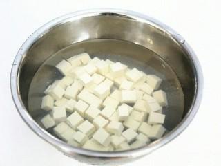 蟹黄豆腐,把豆腐切成小块,然后放入淡盐水中浸泡10分钟。
