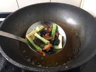官烧目鱼条(天津菜),将冬菇、木耳、黄瓜、冬笋放入漏勺里,用热油汆一下备用。