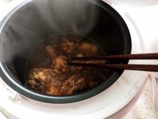 可乐鸡根翅(电饭煲版),约摸15分钟左右的样子,打开锅盖,用筷子把鸡根翅翻个面,然后盖上锅盖继续煮