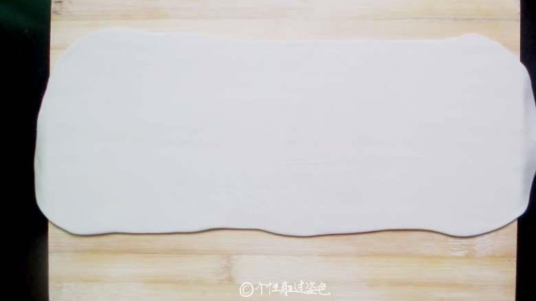 死面卷子,晾凉的面团放到撒了薄面的案板上,擀成厚度约为1-2毫米的长方形面片。