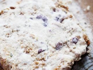 超好吃的人气草莓雪花酥,趁热放入撒上一层奶粉的平板上,压平整,表面撒上奶粉。