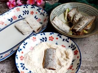 茄汁带鱼(罐头),取面粉一份放入盘中,如图裹面粉。