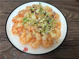 蒜蓉虾仁蒸粉丝,烧热炒锅,倒入一点食用油,将蒜蓉和葱头部分炒香,铲起均匀铺在虾仁上面。