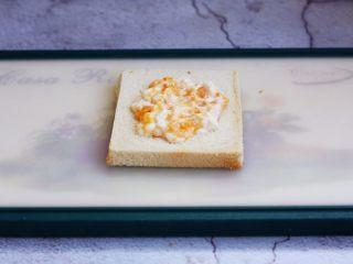 芒果酸奶三明治,将适量的芒果酸奶涂抹在吐司切片中间,四周留2cm的空白边。