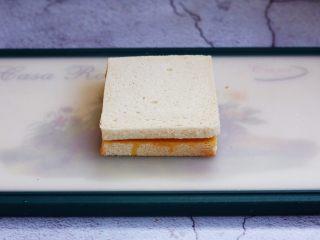 芒果酸奶三明治,将另外一片吐司切片放在上边,轻轻压一下,使两片吐司切片粘在一起。